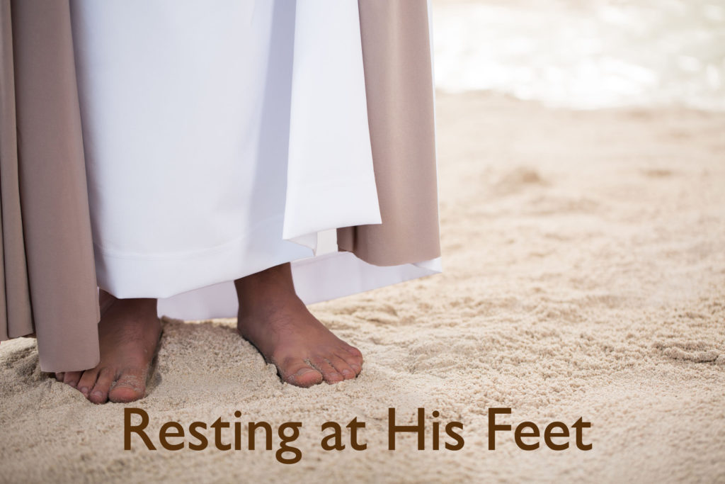 Feet of Jesus Christ standing on sand